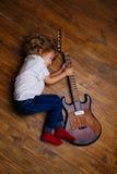 Little Boy som sover och kramar gitarren Arkivbilder