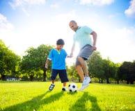 Little Boy som spelar fotboll med hans fader royaltyfria bilder