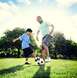 Little Boy som spelar fotboll med hans fader Concept Arkivfoton