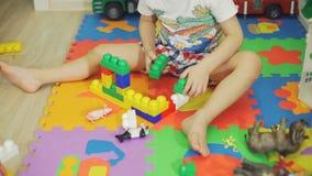 Little Boy som spelar med färgrika plast- tegelstenar arkivfilmer