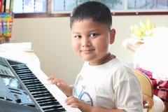 Little Boy som spelar pianot Arkivfoto