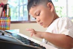 Little Boy som spelar pianot Arkivfoton