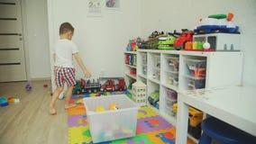 Little Boy som upp väljer leksaker i en plast- ask stock video