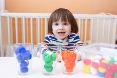 Little boy sorts details by color Stock Images