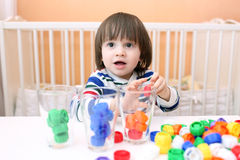 Little boy sorts multicolored details by color Royalty Free Stock Images