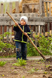 Little boy with a spade in the garden. Village life Royalty Free Stock Photo