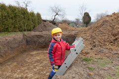 Small worker helped your father. Little boy with a spade helps parents during the construction of the pool royalty free stock photos