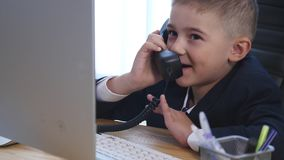 Little boy speaking on phone in the office Royalty Free Stock Photo