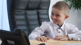 Little boy speaking on phone in the office and drink juice Stock Photography