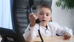 Little boy speaking on phone in the office and drink juice Stock Image