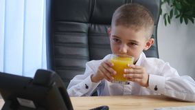 Little boy speaking on phone in the office and drink juice Royalty Free Stock Image