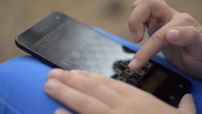 Little Boy spelar schack på Smartphone arkivfilmer