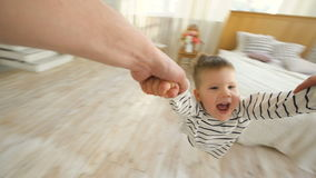 Little boy spinning around and around laughing and smiling at the end of his fathers arms at home stock video