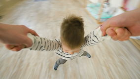 Little boy spinning around and around laughing and smiling at the end of his fathers arms at home stock footage