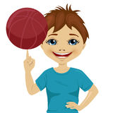 Little boy spinning basketball ball with his finger. Over white background Stock Photo