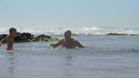Little boy splashes water on happy daddy in sea slow motion