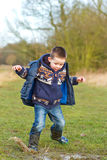 Little boy splashing in a puddle in the field Royalty Free Stock Images