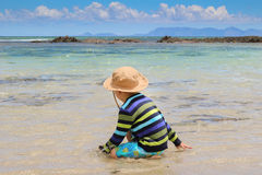 Little boy splashing in shallow sea water Stock Photo