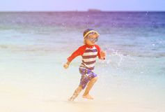 Little boy splashing water on tropical beach Stock Image