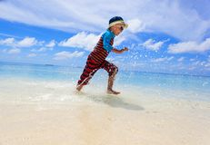 Little boy splashing water on tropical beach Stock Photos