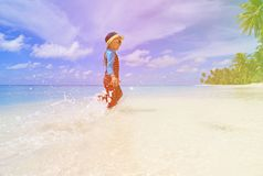Little boy splashing water on tropical beach Royalty Free Stock Photos