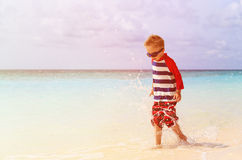 Little boy splashing water on tropical beach Royalty Free Stock Image