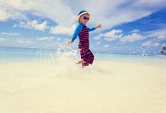 Little boy splashing water on tropical beach Royalty Free Stock Images