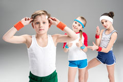 Little boy in sportswear adjusting eyeglasses and sporty girls standing behind. Children sport concept royalty free stock photo