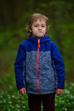 Little boy in spring forest with many flowers Stock Photo