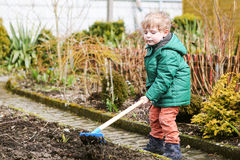 Little boy in spring with garden hoe, planting and gardening. Outdoors Royalty Free Stock Photography