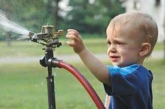 Little boy in a sprinkler Stock Photos