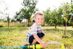 Little boy at the sprinkler having fun, summer garden Royalty Free Stock Image