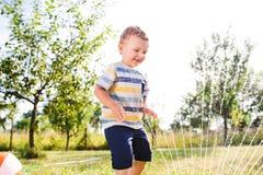 Little boy at the sprinkler having fun, summer garden Stock Image