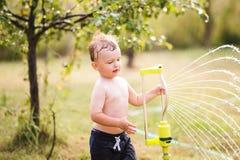 Little boy at the sprinkler having fun, summer garden Royalty Free Stock Photos