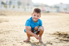 Little boy squat in sand on beach Royalty Free Stock Image