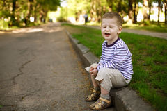 Little boy squints sitting on the curb Royalty Free Stock Images
