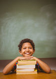 Little boy with stack of books in classroom Stock Image