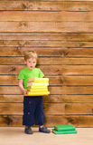 Little boy with stack of books at wooden wall Royalty Free Stock Photos