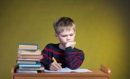 Little Boy stanco infelice che fa il suo compito Scuola di formazione alla perforazione Studi immagine stock libera da diritti