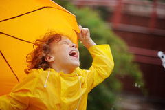 Little boy stand in the drizzle and tongue catches rain drops. Stock Photo