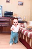 Little boy stand on hardwood floor in home. Little boy stand on hardwood floor, hold sofa in typical home interior Royalty Free Stock Image
