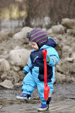 Little boy stand with red shovel in pool. On street Royalty Free Stock Photos
