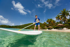 Little boy on stand up paddle board Stock Images
