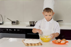 Little boy standing baking cakes in a toque Royalty Free Stock Photos