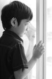 Little boy standing behind the door black and white Royalty Free Stock Photo
