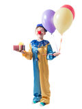 Little boy standing in a clown suit with a red nose and holding a three balloons and a box with a bow Royalty Free Stock Photo