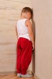 Little boy standing in a corner sulking Stock Image