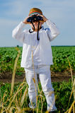 Little boy standing in farmland using binoculars Royalty Free Stock Images
