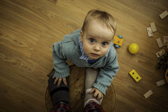A little boy standing on the floor near stool with toys around Stock Photos