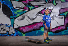 Little boy standing in front of vibrant graffiti Stock Images
